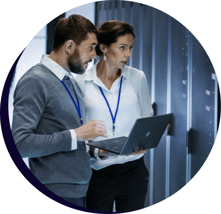 Man and woman looking at a large computer server and holding laptop