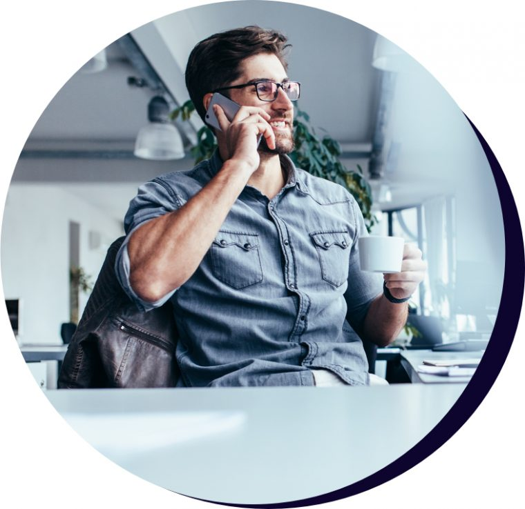 Man in collared shirt drinking a coffee at his office desk while on a mobile call