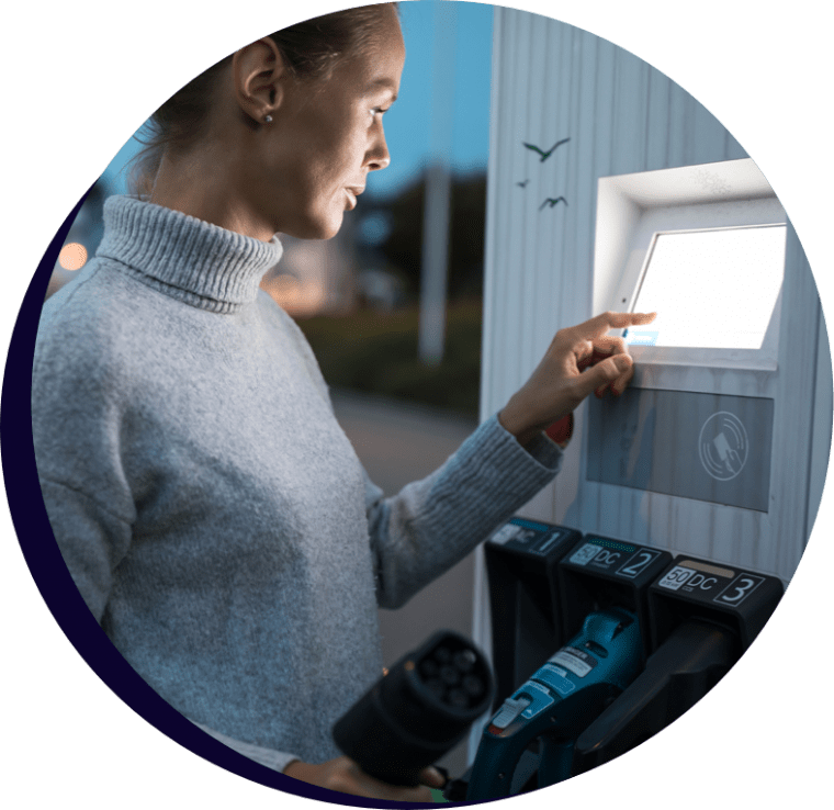 A lady at dusk using the touch screen of an electric car recharging station