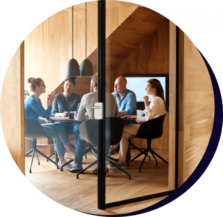 Two men and three women sitting around a round boardroom table.